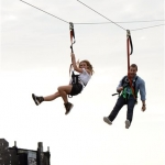 Image of Man and Woman hanging from a zip line